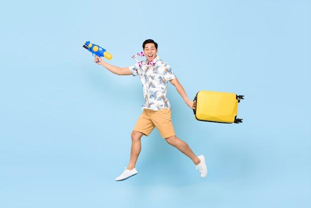 Springende knappe aziatische toeristenmens die met waterkanon en bagage reizen tijdens festival songkran