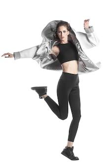 Springende vrouw gekleed in een jas - parka, geïsoleerd op wit Premium Foto