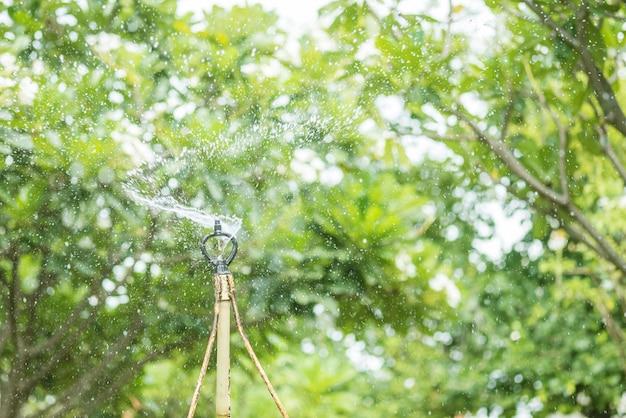 Springer, automatisch sproeisysteem werkt in de tuin in vintage toon