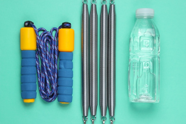 Springtouw, fles water, expander. sportuitrusting op blauwe achtergrond. bovenaanzicht