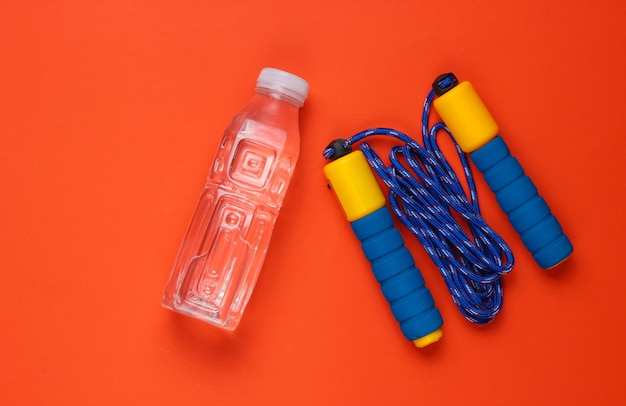 Springtouw, fles water. sportuitrusting op oranje achtergrond.