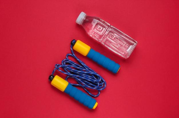 Springtouw, fles water. sportuitrusting op rode achtergrond. kopieer ruimte. bovenaanzicht