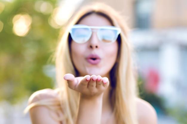 Sprint positief portret van gelukkige vrolijke jonge vrouw die luchtkus naar u verzendt, een duidelijke bril draagt, focus aan de kant, pastelkleurige kleuren.