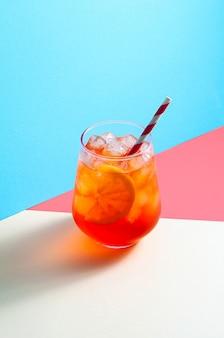 Spritz cocktail in glas met ijs en sinaasappelschijfje op trendy kleurrijke achtergrond