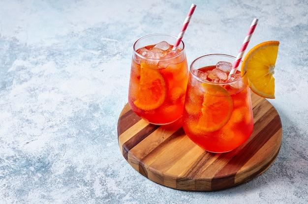Spritz cocktail in glazen met ijs en sinaasappelschijfje op een houten bord op lichtblauwe achtergrond.