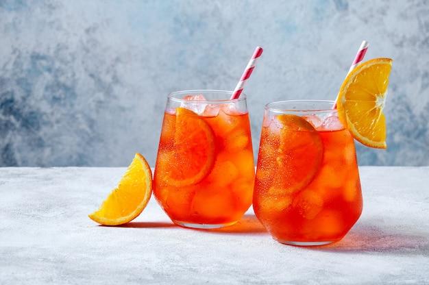 Spritz cocktail in glazen met ijs en sinaasappelschijfje op lichtblauwe achtergrond.