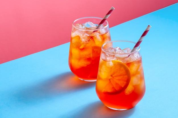 Spritz cocktail in glazen met ijs en sinaasappelschijfje op trendy kleurrijke achtergrond