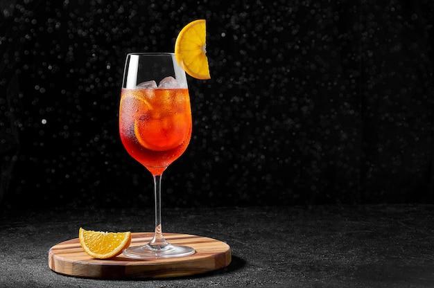Spritz cocktail in wijnglas met opspattend water op een houten bord op donkere achtergrond