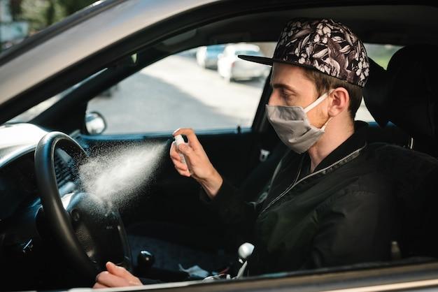 Sproeien van antibacteriële ontsmettingsspray op stuur, desinfectieauto, infectiecontroleconcept. voorkom coronavirus, covid-19, griep. mens die in medisch beschermend masker draagt dat een auto drijft.