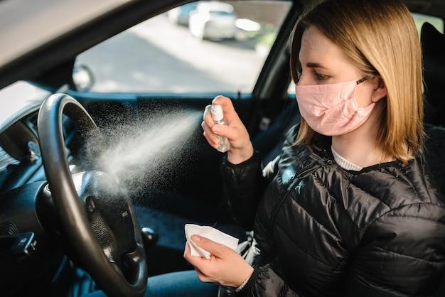 Sproeien van antibacteriële ontsmettingsspray op stuur, desinfectieauto, infectiecontroleconcept. voorkom coronavirus, covid-19, griep. vrouw die in medisch beschermend masker draagt dat een auto drijft.