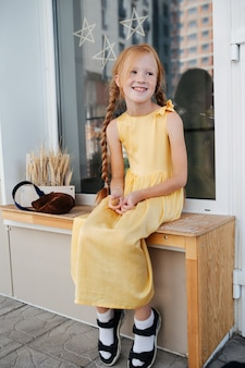 Sproeten gember meisje in een levendige gele jurk zit op een bankje. voeten die in de lucht hangen, kijkend aan de andere kant.