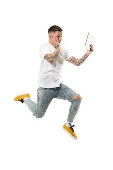 Sprong van jonge man over witte studio achtergrond met behulp van laptop tijdens het springen.