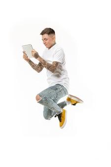 Sprong van jonge man over witte studio achtergrond met behulp van tablet tijdens het springen.