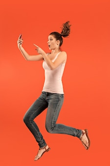 Sprong van jonge vrouw over blauwe studioachtergrond die laptop of tabletgadget gebruikt tijdens het springen. lopend meisje in beweging of beweging. menselijke emoties en gezichtsuitdrukkingen concept.