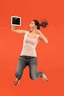 Sprong van jonge vrouw over blauwe studioachtergrond die laptop of tabletgadget gebruikt tijdens het springen. runnin meisje in beweging of beweging. menselijke emoties en gezichtsuitdrukkingen concept. gadget in het moderne leven