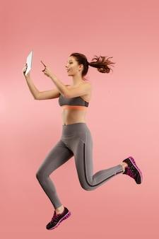 Sprong van jonge vrouw over blauwe studioachtergrond met behulp van laptop of tabletgadget tijdens het springen. runnin meisje in beweging of beweging.