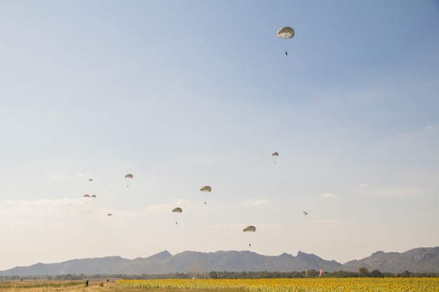 Sprong van parachutist met witte parachute