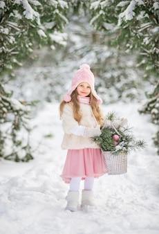 Sprookje een mooi meisje in een witte bontjas met een witte grote mand met dennentakken in een besneeuwde winterbos.