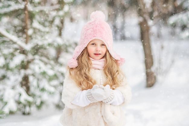 Sprookje portret van een mooi meisje in een witte bontjas roze sneeuw hoed in haar handen.