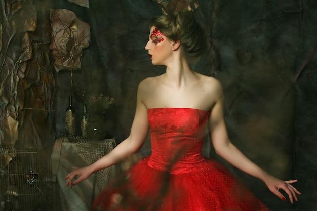 Sprookje. theater. vrouw in rode jurk. fantastisch kapsel en make-up. fantasie.