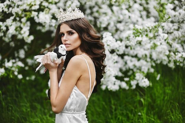 Sprookjesachtige foto - mooie en sexy bruinharige modelvrouw met een kroon op haar hoofd in lingerie, met een duif in haar armen in het groene bos