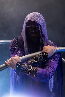 Sprookjesachtige karaktermoordenaar in een paarse mantel met een kap met twee grote cyr-wielringen