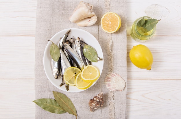 Sprot met kruiden en citroen, olie, schelp.