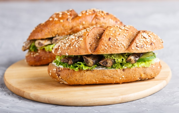 Sprottensandwiches met sla en roomkaas op houten raad op een grijze concrete achtergrond.