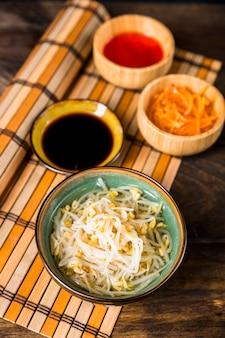 Sprout bonen kom met soja en rode chili sauzen op placemat