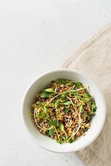 Spruiten van verschillende zaden met groen blad in kom op witte, verticale bovenaanzicht