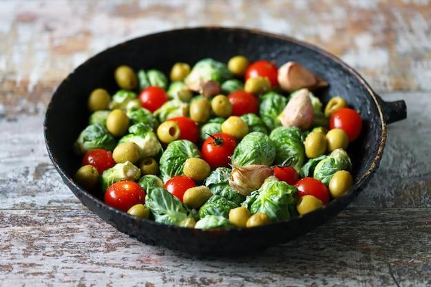 Spruitjes met groenten en kruiden in een pan