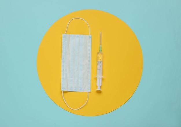 Spuit en medisch masker op een blauw met gele cirkel in het midden