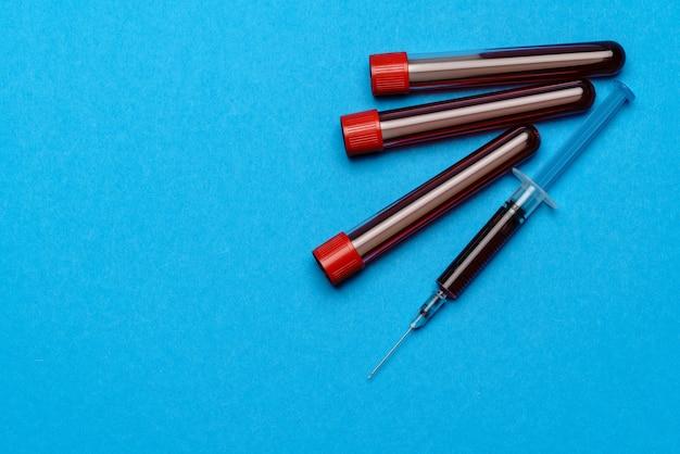 Spuit en plastic reageerbuis met bloedmonster met copyspace