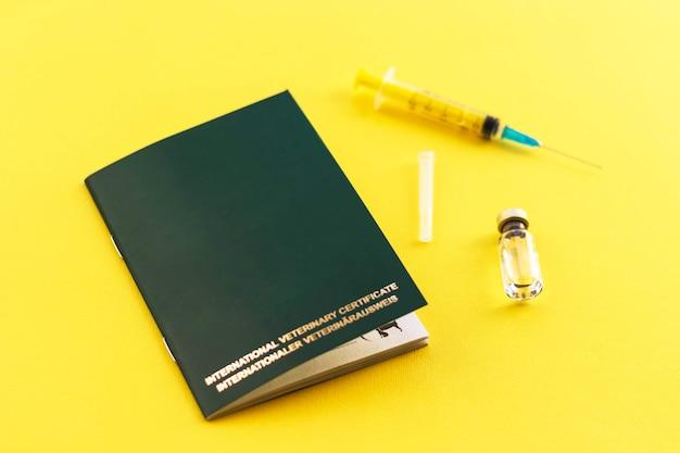 Spuit, glazen flacon met vloeistof en dierenpaspoort voor het aangeven van vaccinaties en chipnummer.