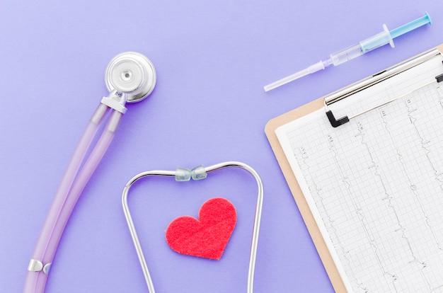 Spuit; medisch rapport over klembord; hart met stethoscoop op paarse achtergrond
