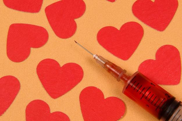 Spuit naast rood hartdocument ontwerpen in lichtoranje