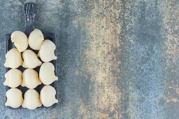 Spuit pasta's in de bak, op het marmeren oppervlak.