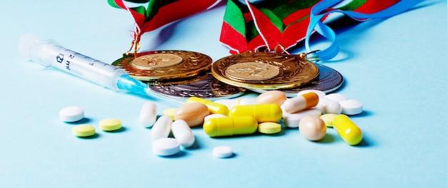 Spuit, pillen en medailles op een blauwe achtergrond. doping in de sport. misbruik van anabole steroïden voor sport. sportfraude. atleten met doping.