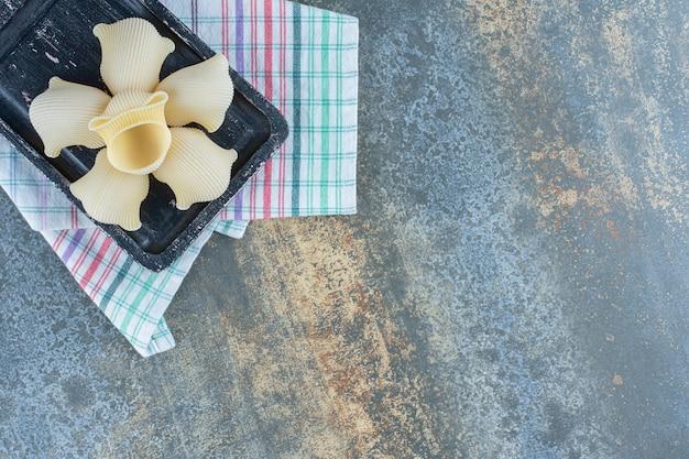 Spuit rigate pasta in de houten plank op de handdoek op het marmeren oppervlak.