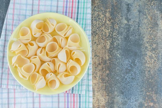 Spuit rigate pasta in de kom, op de handdoek op het marmeren oppervlak.