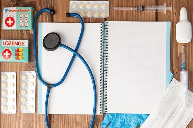 Spuit, stethoscoop, blanco pagina kladblok, verband, pil en handschoenen op de dokterstafel. medische diagnose of doktersrecept