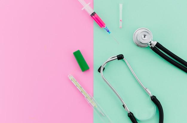 Spuit; stethoscoop; thermometer op roze en mintgroene achtergrond