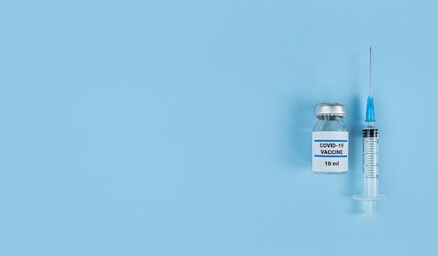 Spuit voor eenmalig gebruik en medische fles met coronavirusvaccin op een blauwe achtergrond met kopie ruimte.