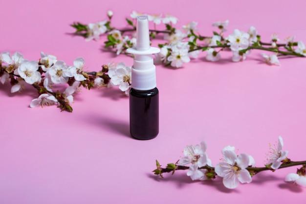 Spuitbus voor de neus. spuitbus op een roze achtergrond. indeling. bloeiende tak. allergie