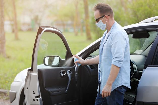 Spuiten antibacteriële ontsmettingsmiddel spray op auto, infectiecontrole concept. voorkom coronavirus, covid-19, griep. mens die in medisch beschermend masker draagt dat een auto drijft. desinfecterende doekjes.