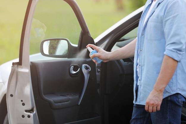 Spuiten antibacteriële ontsmettingsmiddel spray op stuurwiel auto, infectie controle concept. voorkom coronavirus, covid-19, griep. mens die in medisch beschermend masker draagt dat een auto drijft. desinfecterende doekjes.