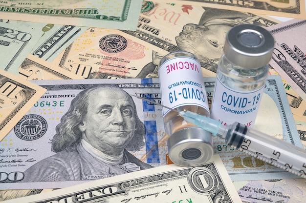 Spuiten en covid-19-vaccinflesje bovenop de amerikaanse dollar.