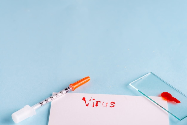 Spuiten en reageerbuis met bloed met wit papier en het opschrift virus