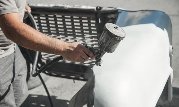 Spuitpistool in de hand van een schilder. autodetails schilderen