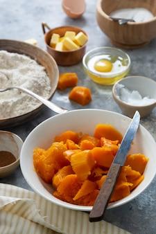 Squashtaart koken. ingrediënten voor het koken van pompoentaart. herfst dessert. bakkerij achtergrond